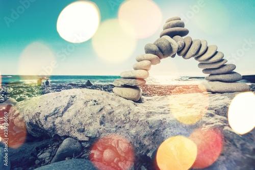 Zen basalt stones on sunset beach background - 230986669