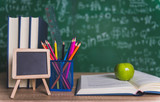 Back to school supplies. Books and blackboard on wooden background. - 231004441