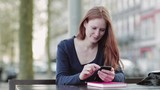 A happy young woman sits on a bench on a city street and chats or texts on a smartphone. - 231007022