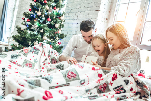 Family hugging near christmas tree on the bed. New year's morning - 231018805
