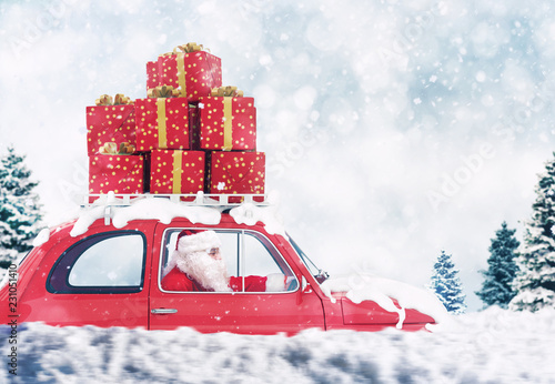 Poster Santa Claus on a red car full of Christmas present with winter background drives to deliver