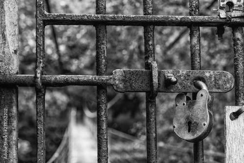 Ein Eisentor mit Gitter und Eisenschloss versperrt den Zugang zur Hängebrücke in schwarz-weiß