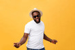 Young black man top dancing isolated on a yellow background.