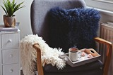Cozy home with cup of tea with steam and blanket. Hygge home interior