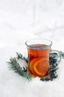 A glass cup of hot tea with slices of orange on the snow. Fir branches. Christmas mood