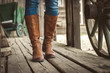 Walking on wooden floor with leather boots on old retro ranch.