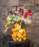 Bouquet of wild flowers and colorful autumn leaves. Autumnal bouquet in a glass vase with quince fruits. Old wall in the background. - 231077454