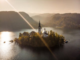 Aerial view of island of lake Bled with Pilgrimage Church of the Assumption of Maria in city of Bled in Slovenia at sunset. - 231084841