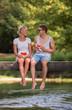 Leinwandbild Motiv couple enjoying watermelon while sitting on the wooden bridge