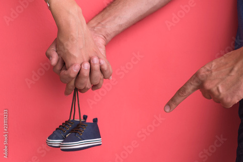 Leinwanddruck Bild young pregnant couple holding newborn baby shoes