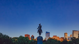 George Washington statue in Boston Public Garden against blue sky and skyline of downtown at dusk, in Boston, USA
