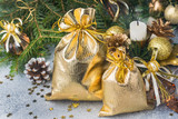 Gold bags with Christmas gifts on the background of Christmas trees and decorations gray background. New year greetings concept. - 231123299