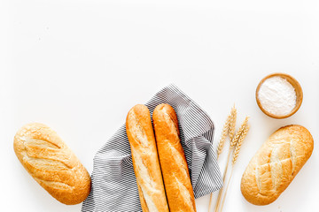 White bread. Fresh rustic homemade bread and loaf on tablecloth decorated with ears and flour on white background top view copy space