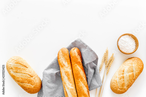 White bread. Fresh rustic homemade bread and loaf on tablecloth decorated with ears and flour on white background top view copy space - 231123423