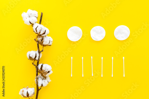 Leinwanddruck Bild Products made of cotton. Bath accessories. Towels, cotton pads and swabs near dry cotton flowers on yellow background top view