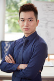 Portrait of handsome businessman in blue shirt standing with arms crossed with confident face - 231127846