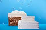 clean white towels, laundry basket and soap bubbles on blue - 231140065