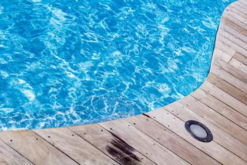 piscine bleue avec plage en bois et éclairage éclairé
