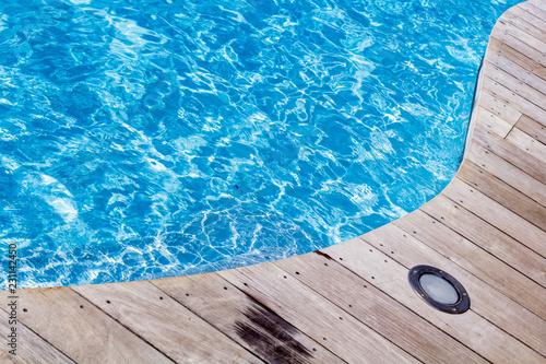 Foto Murales piscine bleue avec plage en bois et éclairage éclairé