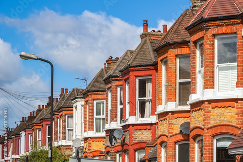 A row of typical red brick British terraced houses in London