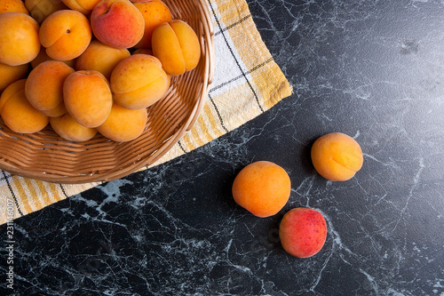 Fresh organic apricots in basket. Group of harvested apricots in basket.. - 231146007
