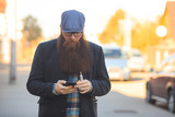 Vape bearded man in real life. Portrait of young guy with large beard in glasses and a gray cap talking on the phone and vaping an electronic cigarette on the street in the village in the autumn. - 231153029