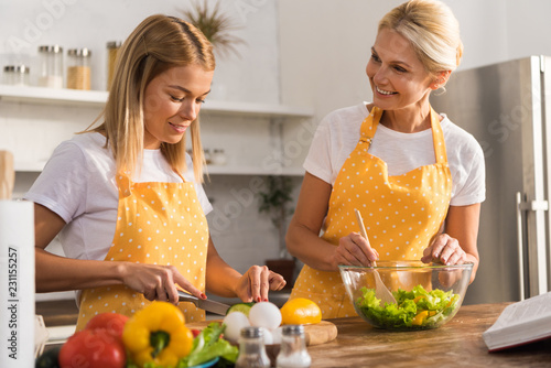 happy mature woman and young daughter cooking vegetable salad together in kitchen