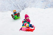 Leinwanddruck Bild - Kids play in snow. Winter sled ride for children