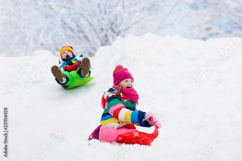 Leinwanddruck Bild Kids play in snow. Winter sled ride for children