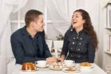 romantic couple drinking tea with cookies and talking - 231162042