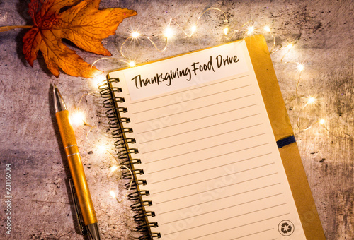 Wall mural Thanksgiving Food Drive list concept on notebook surrounded with bright leaves and decorative lights, flat lay