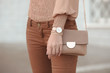 Fashion look autumn woman outfit. Stylish women's beige handbag. Closeup of luxury watch and feminine accessories in pastel colored. Cute beige ladies purse bag. - 231172824