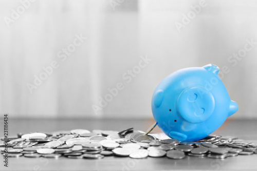 Blue piggy bank on top of coins money for money flow concept and gray background