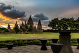 Prambanan temple view with green grass field foreground and cloudy sunrise; background - 231186843