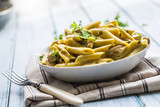 Pasta pene with chicken pieces mushrooms parmesan cheese sauce and herb decoration. Pene con pollo - Italian or medierranean cuisine