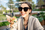 Young woman having a snack with pizza sitting outdoors at the modern public park - 231188687