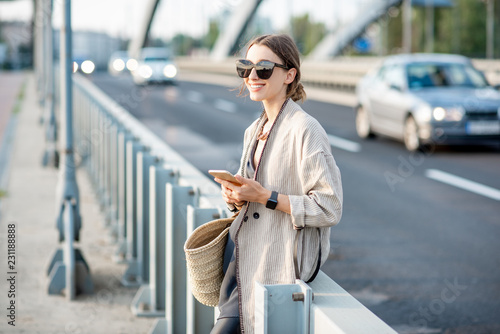 Fridge magnet Lifestyle portrait of a young stylish woman with bag and phone outdoors on the modern bridge