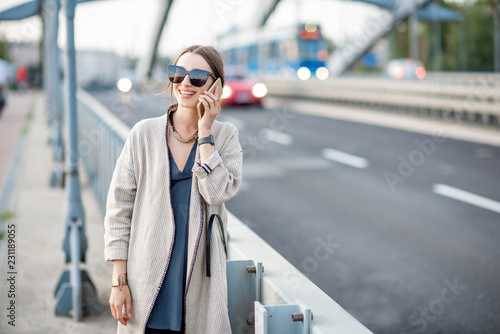 Lifestyle portrait of a young stylish woman with bag and phone outdoors on the modern bridge - 231189055