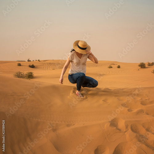 Young woman in jeans and straw hat. Girl in the desert - 231189428