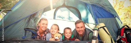 Leinwandbild Motiv Smiling family lying in the tent