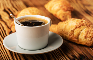 Cup of coffee with croissants on a wooden table