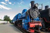 Old steam locomotive beside a railway station platform. Retro train.