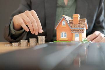 hand putting coins on stack with house model. saving money for buying house. real estate property investment