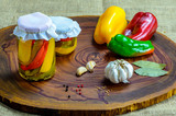 Preserved vegetarian food concept.Canned red, green an yellow peppers in a jar on wooden background. - 231205460