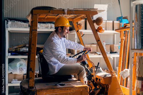 Man riding forklift. On head helmet. Storage interior.