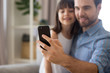 Leinwandbild Motiv Smiling father and little cute preschool daughter looking at smartphone screen taking selfie portrait photography sitting on couch, focus on male hand close up. Family have fun use technology concept