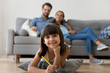 Leinwandbild Motiv Family in living room looking at camera at home. Close up focus on little preschool daughter smiling lying at soft cushion on warm wooden floor draws hold pencil, young parents resting sitting on sofa