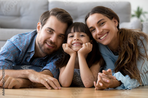Leinwandbild Motiv Multi-ethnic diverse family lying at cushions on warm floor in living room at modern home smiling looking at camera. Young mother adorable daughter handsome father feels happy spend free time together