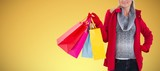 Composite image of blonde in winter clothes holding shopping - 231236613