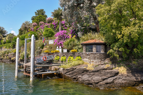 Molo sugli scogli dell'Isola Madre sul Lago Maggiore con piante fiorite e cielo blu in estate, Piemonte, Italia